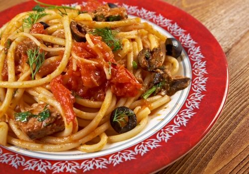 Spaghetti alla puttanesca  salty Italian pasta dish.ingredients are typical of Southern Italian cuisine: tomatoes, olive oil, olives, capers and garlic.